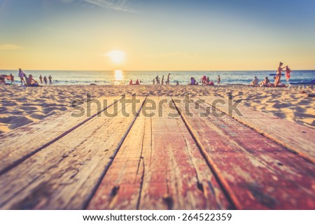 Top of wooden table at sunset beach in Thailand, Vintage filter effect - stock photo