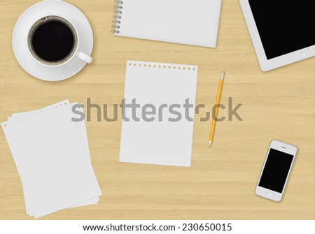 Top office table with cup of coffee, paper, note, pencil, tablet and smartphone - stock photo