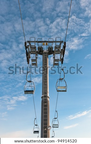 Top part of ski-lift support and few chairs on ropes