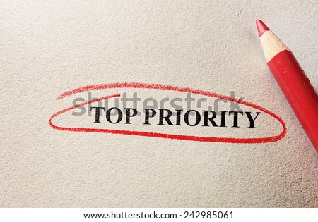 Top Priority text circled in pencil on textured paper                                - stock photo