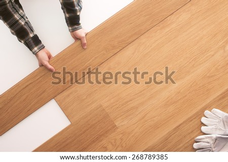 Top quality wooden floor installation at home, carpenter's hands placing a tile on the floor top view - stock photo