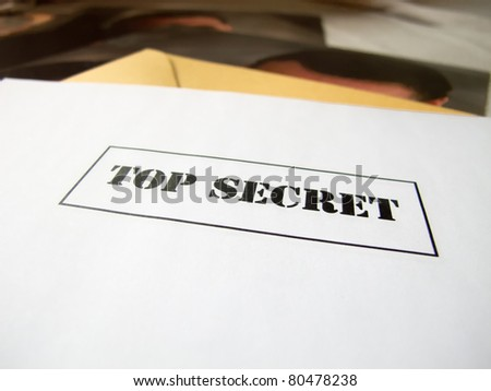 top secret envelop on a desk above hidden pictures - stock photo