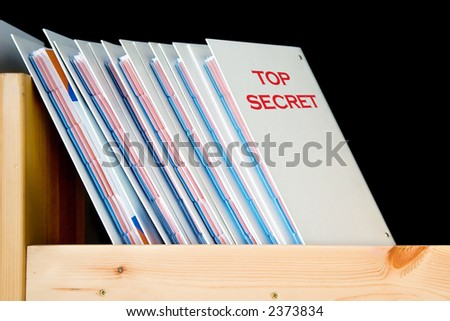 Top secret folders on the shelf, isolated on black - stock photo