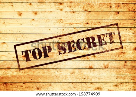 Top secret stamp on wood texture background