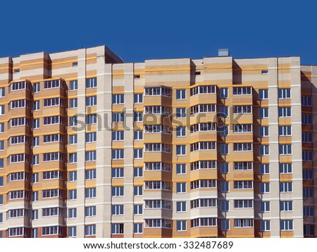 Top section of multi-storey modern building constructed from bricks over clear blue sky - stock photo