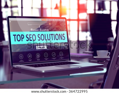 Top SEO - Search Engine Optimization - Solutions Concept. Closeup Landing Page on Laptop Screen  on background of Comfortable Working Place in Modern Office. Blurred, Toned 3d Image. - stock photo