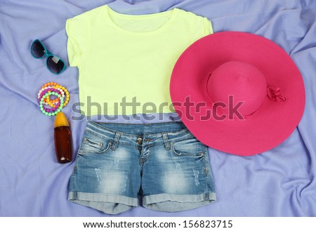Top, shorts and beach items on bright purple background - stock photo