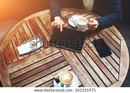 Top shot of a coffee shop table with elegant woman sitting and using touch screen tablet while drink cappuccino, bill check and mobile phone near, flare sun light - stock photo