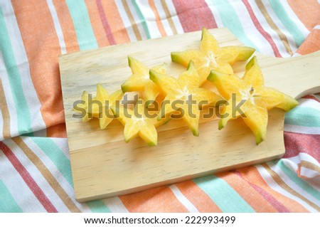 Top shot of starfruit on a wooden chopping board and stripe napkins - stock photo