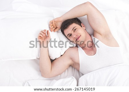 Top side. Young smiling male lying on bed. - stock photo