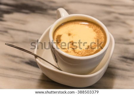 Top view a cup of Giang egg coffee in Hanoi on marble table. Since 1946 the coffee is dripped and brewed in a small cup with filter then addition of well-whisked mixture yolks and other ingredients.