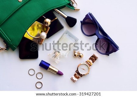 Top view accessories for woman. Stylish sunglasses, green bag , gold watch , lipstick , perfume , rings , smart phone - stock photo