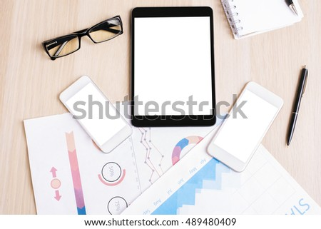 Top view and close up of wooden desktop with blank white tablet, two cellular phones, business report, glasses and supplies. Mock up