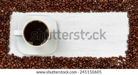 Top view angle of freshly made dark coffee with roasted coffee beans, forming even border, on white wooden table.  - stock photo