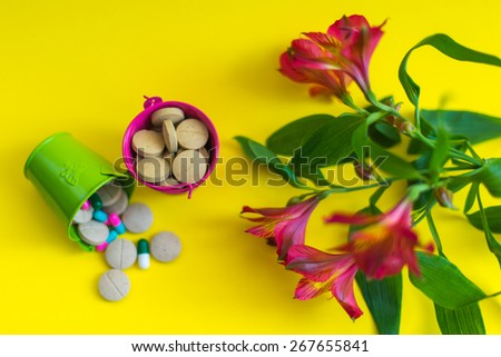 top view at green and pink buckets full of pills with flower at the yellow background  - stock photo