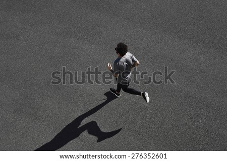 Top view athlete runner training at black road in sportswear at central position. Muscular fit sport model sprinter exercising sprint on city road. Full body length of Caucasian model. - stock photo