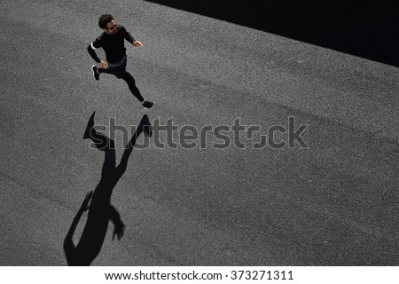 Top view athlete runner training at road in black sportswear at central position. Man running on country road, healthy inspirational fitness lifestyle, sport motivation speed interval training.  - stock photo