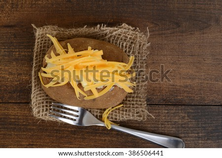 top view baked potato with cheese and butter - stock photo