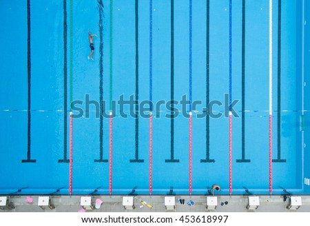 top view bird eye view of blue swimming pool with swimmers and starting platforms