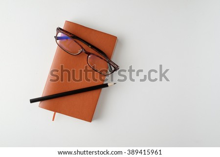 top view blank orange leather diary, pencil and glasses on white desk - stock photo