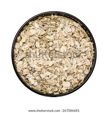 Top view bowl of uncooked rolled oats isolated on white background. Oat flakes for breakfast. Healthy homemade oatmeal breakfast in a bowl close up - stock photo