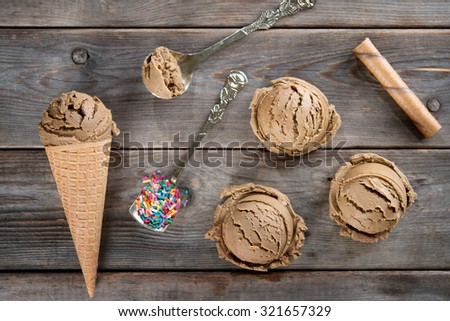 Top view brown ice cream in waffle cone on old rustic vintage wooden background.  - stock photo