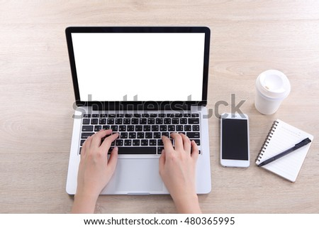 Top view business woman using mock up laptop with smartphone on wooden desk