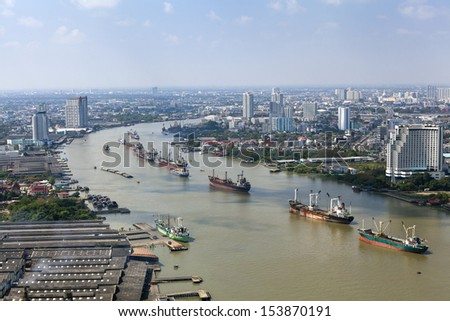 top view cargo ship on Chao Phraya river and city scape in Bangkok, Thailand