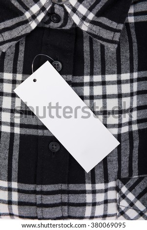 Top view close up black and white plaid shirt with price tag background - stock photo