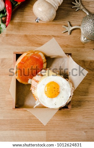 Top view. Close up mini burger. Delicious hamburger with fried eggs, lettuce, cheese, ketchup and bread on a wooden table. American cuisine, copy space. Food and drink concept.