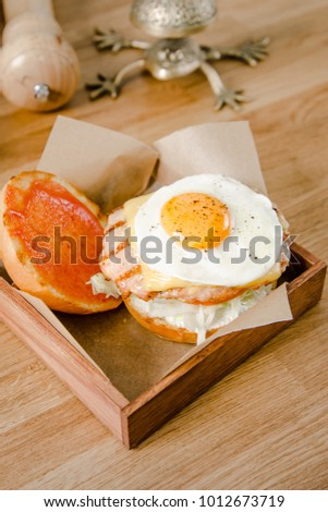 Top view. Close up mini burger. Delicious hamburger with fried eggs, lettuce, cheese, ketchup and bread on a wooden table. American cuisine. Food and drink concept.