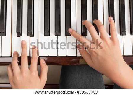 Top view close up of female's both hands playing piano