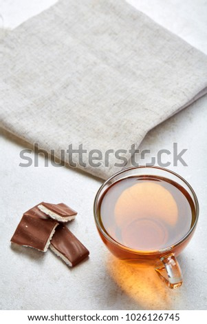 Top view close up picture of tea in glass cup with chocolate isolated on white background, vertical