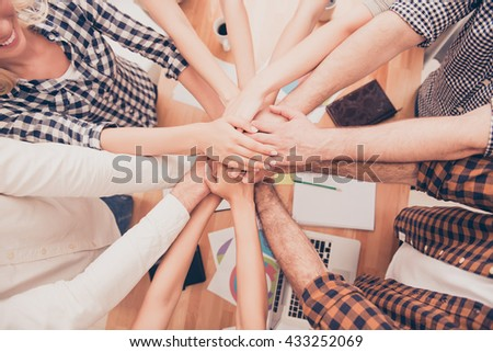 top view closeup photo of businesspeople  putting their hands on top of each other  at conference - stock photo