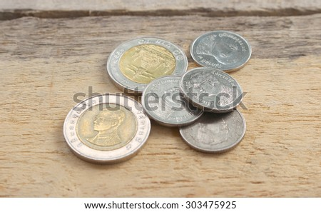 Top view coins on old wooden desk with copy space on bottom. - stock photo