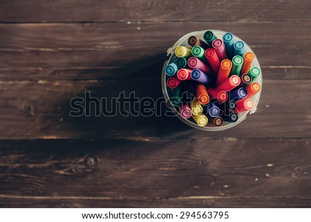 Top view, colorful felt pens on dark wooden table. Toned photo, shallow depth of field. - stock photo