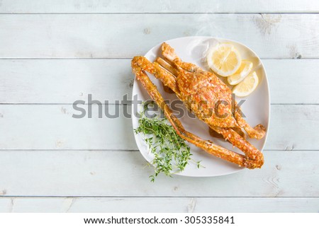 Top view cooked delicious hot and spicy sauce blue crab on white plate, at bright wooden background. Fresh cook with hot smoke steams. - stock photo