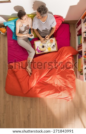 top view couple having breakfast in bed, their bedding is bright colors and sunny interior - stock photo