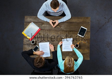 Top view creative photo of business people sitting at dark wooden vintage table. Employers having meeting. Concept for successful interview. There are electronic gadgets and documents at table - stock photo