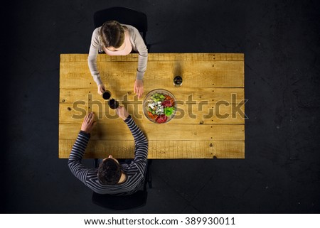 Top view creative photo of couple sitting at wooden vintage table. Man and woman having romantic dinner. They with cheese plate and glasses with wine - stock photo