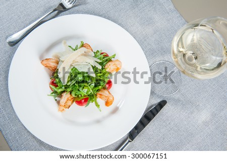 Top view Delicious salad with shrimps, arugula, cherry tomatoes and Parmesan cheese, seasoned with balsamic sauce on served for dinner restaurant table  - stock photo
