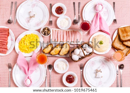 Top view__Easter breakfast or brunch table setting .two pink egg bunnys & white rabbit on dishes