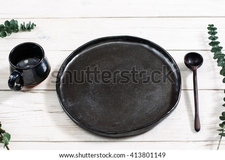 Top view empty black dishes and cutlery on rustic wooden table. Ceramic black plate, cup and spoon on white wooden background. Flat lay of handmade black ceramics on white wooden table.  - stock photo