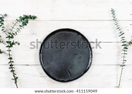Top view empty black plate on rustic wooden table. Ceramic black plate on white wooden background with free space. Flat lay of handmade black dish on white wooden table.  - stock photo