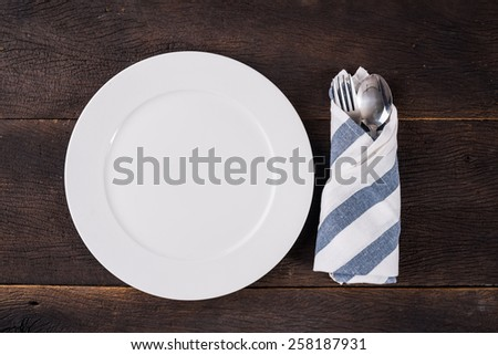 Top view empty plate on dinner table with fork and spoon. - stock photo