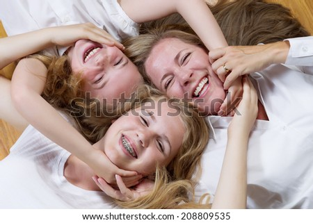 Top view, facing forward, of mother and her daughters lying on oak wooden floor while all joining hands and faces together  - stock photo