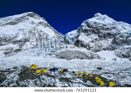 Top view for Group of climbers ' bright yellow color tents on the Khumbu glacier in area of Everest base camp with himalaya mountain range in background during a clear blue sky day