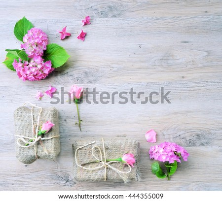 top view frame of gifts ,flat lay gifts and flowers ,on a wooden vintage background with copy place - stock photo