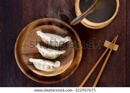 Top view fresh dumplings with hot steams on wood plate with chopsticks. Chinese food on rustic old vintage wooden background.  - stock photo