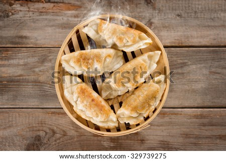 Top view fresh pan fried dumpling on bamboo basket. Chinese food with hot steams on rustic vintage wooden background.  - stock photo